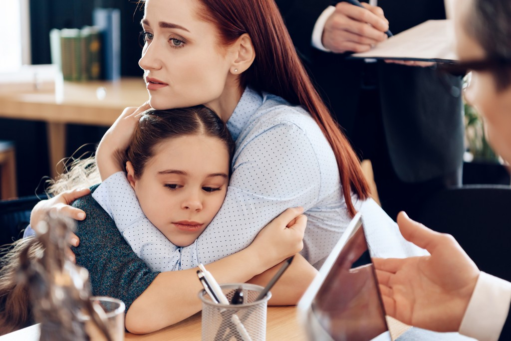 mother hugging her daughter in the attorney's office
